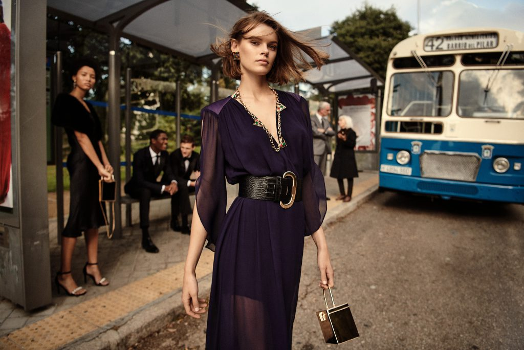 A girl wearing a long purple dress and a black leather skirt. The dress is accessorizd with a silver necklace and a black bag