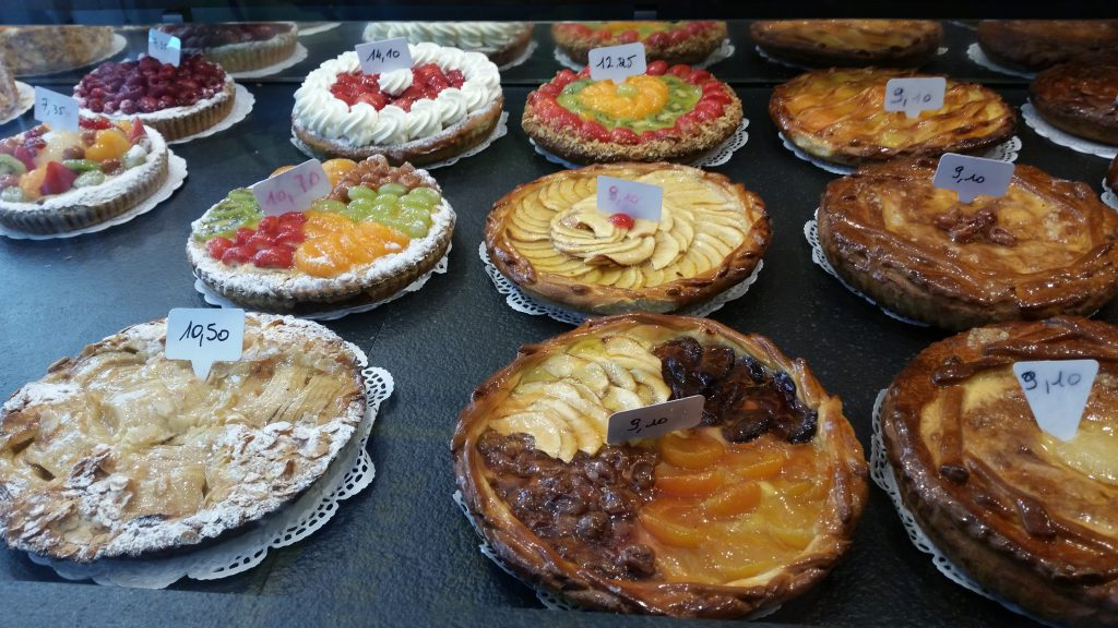 Cakes decorated with apples and various fruit in the bakery Shamp in Liege, Belgium