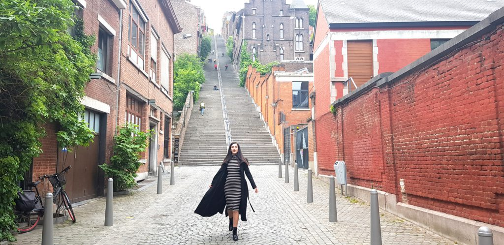 A girl posing in front of the Montange de Bueren, a 374 step staircase in Liège, Belgium