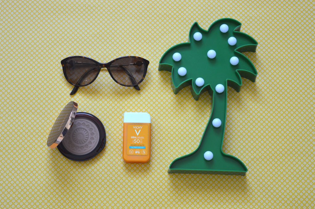 Summer products on yellow background (sunglasses, sunscreen and bronzer)