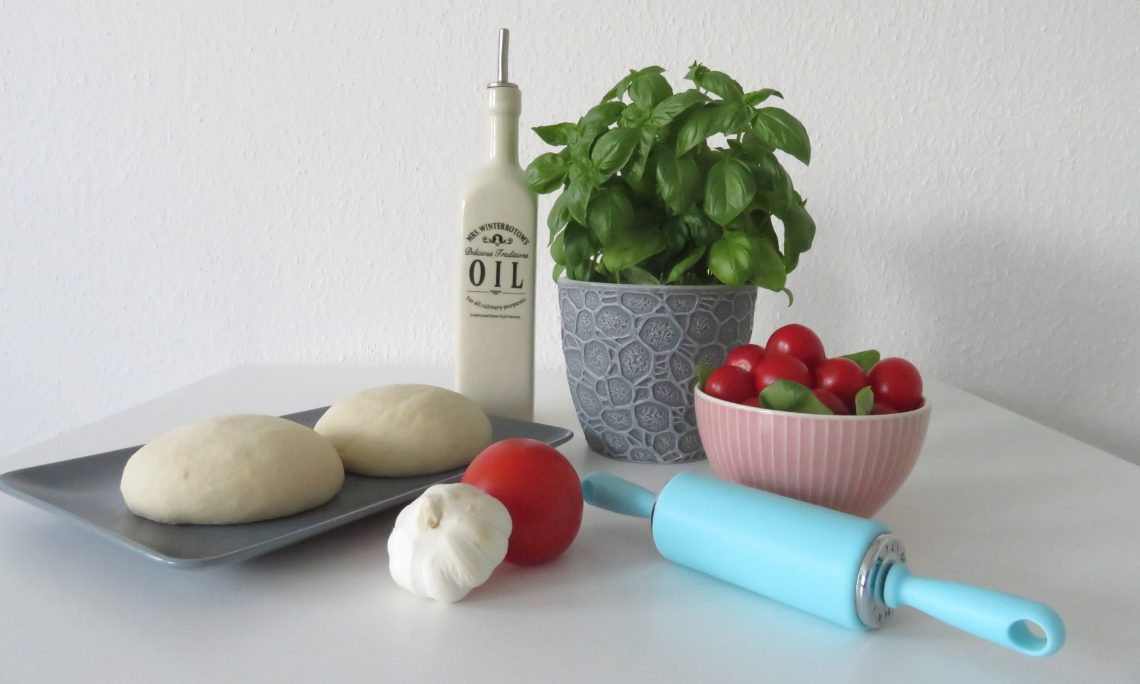 A table with the ingredients for a pizza: basil, tomatoes, garlic, olive oil and pizza dough