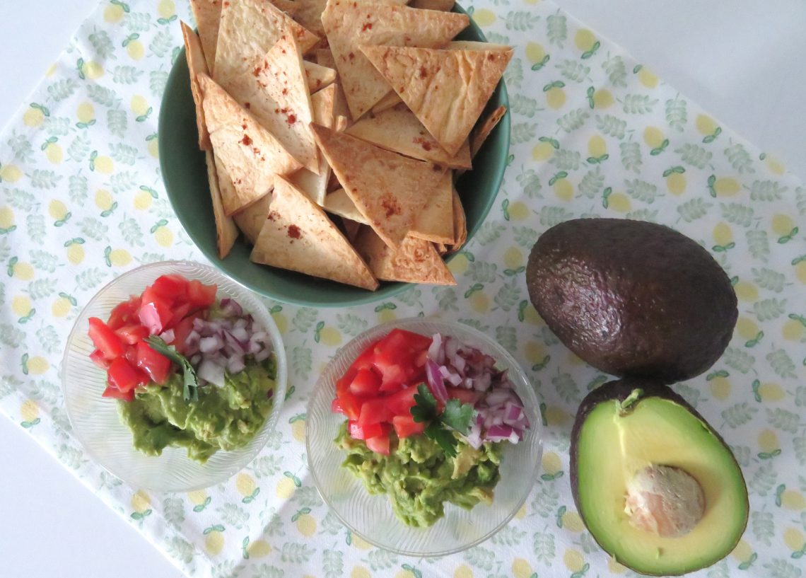A bowl of chips, two bowls of homemade guacamole dip, a guacamole on a tablecloth on a white table