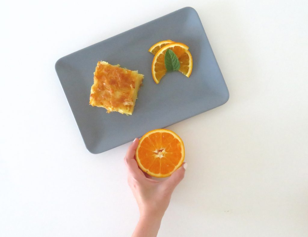 A grey plate with a piece of orange pie and some slices of orange next to it