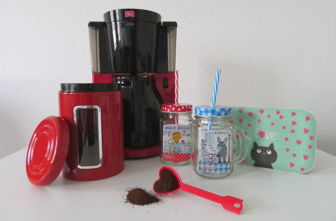 A podless coffee maker, two glass containers and reusable lunchboxes on a table