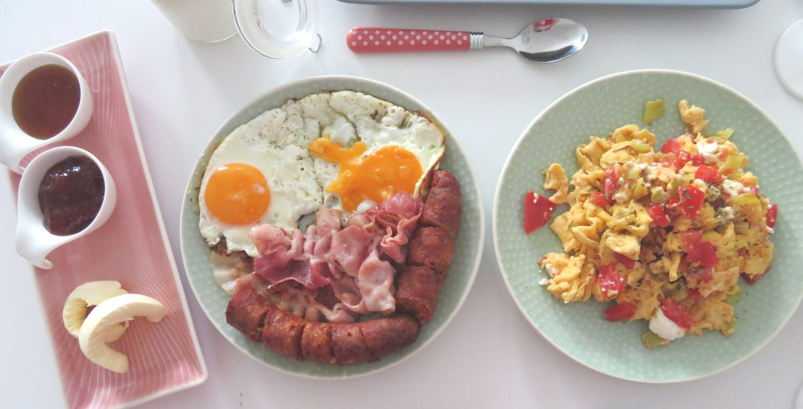 A table with brunch at home such as eggs with bacon and sausage, scrumbled eggs and marmelade