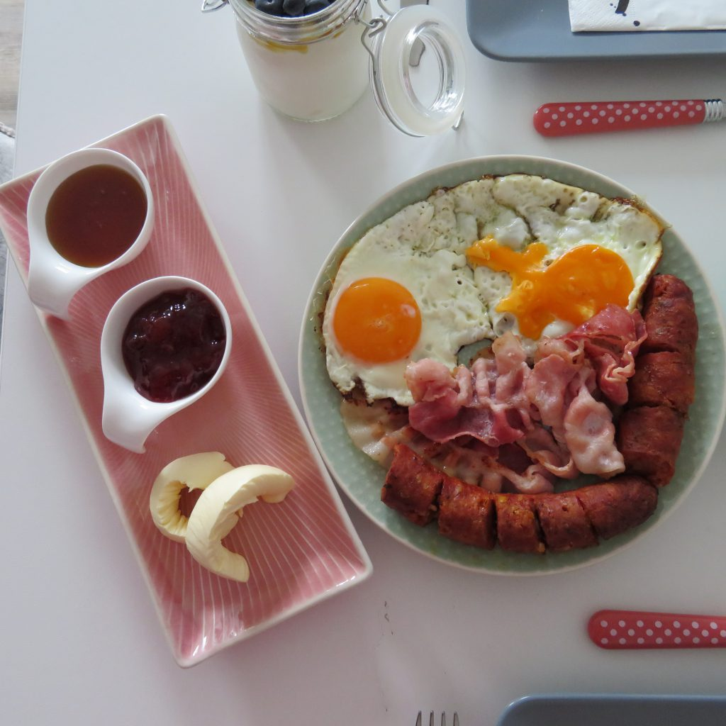 Eggs with bacon and rural style greek sausage on a white table